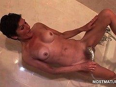 Skinny mature fucks herself with shower head
