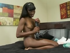 Black teen and big dildos have a hot solo scene in bed