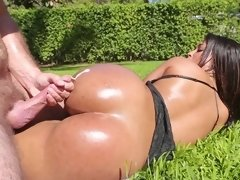 A sweet Latina is getting on her knees on the grass by the pool