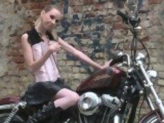 Cute teen is amazed by a big bike
